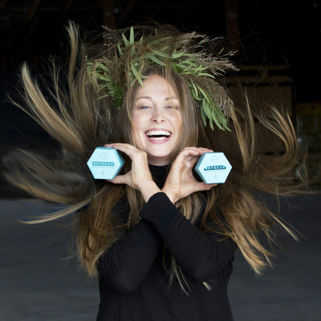 Nauravainen nainen pitää käsissään kahta sinistä Luonkos luonnonkosmetiikan puhdistuskakkupakkausta.