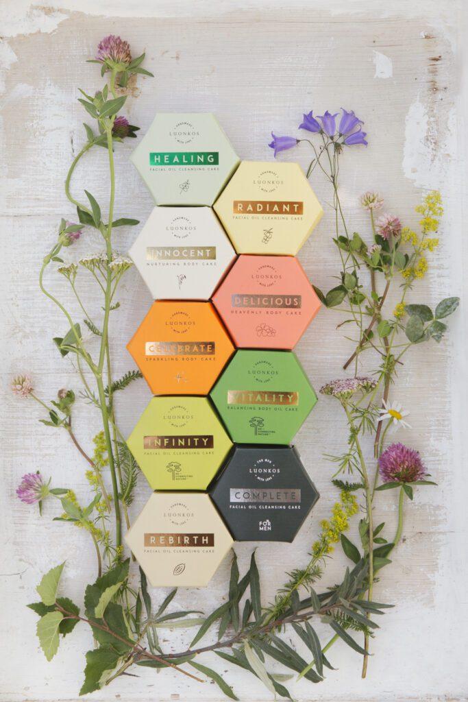 Luonkos luonnonkosmetiikan monivärilliset pakkaukset luonnonkukkien ympäröimänä.