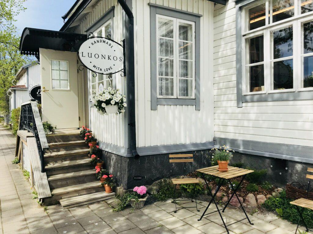 Luonkos lifestyle-myymälän julkisivu ja portaat sisälle valkoiseen puutaloon.