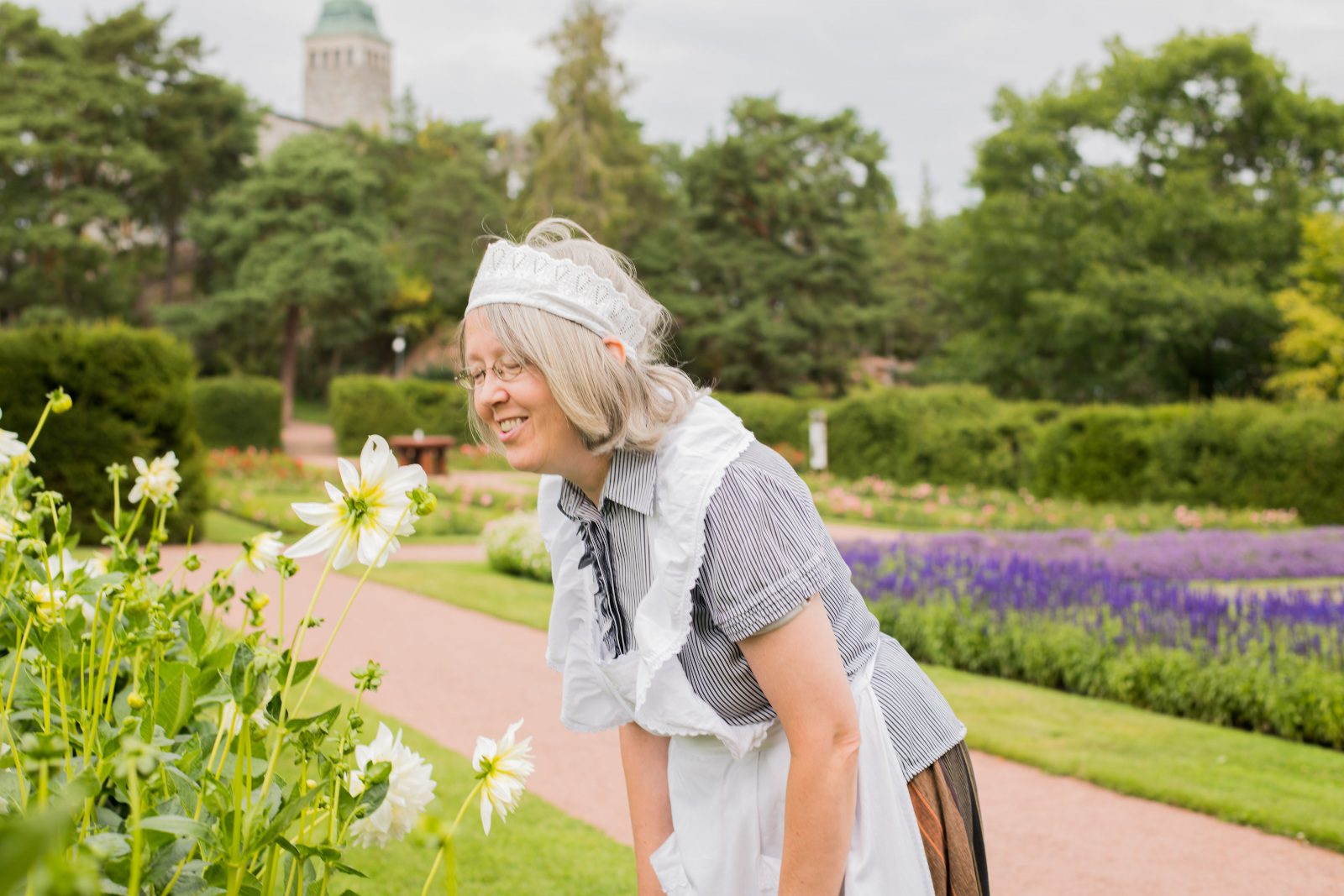 Hymyilevä Mamselli-opas haistelee isoa valkoista kukkaa Kultarannan puutarhassa.
