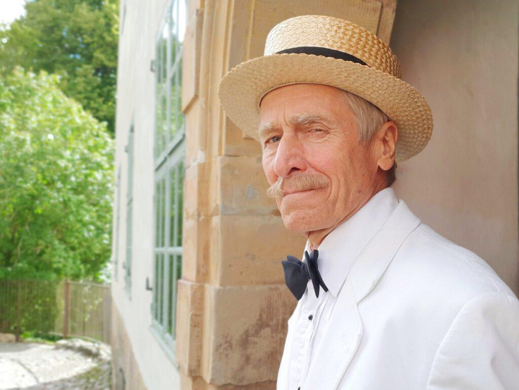 Näyttelijä Petri Rajalan esittämä Mannerheim katsoo kameraan, valkoinen takki, rusetti sekä olkihattu päässään. Taustalla näkyy Louhisaaren kartanon julkisivua.