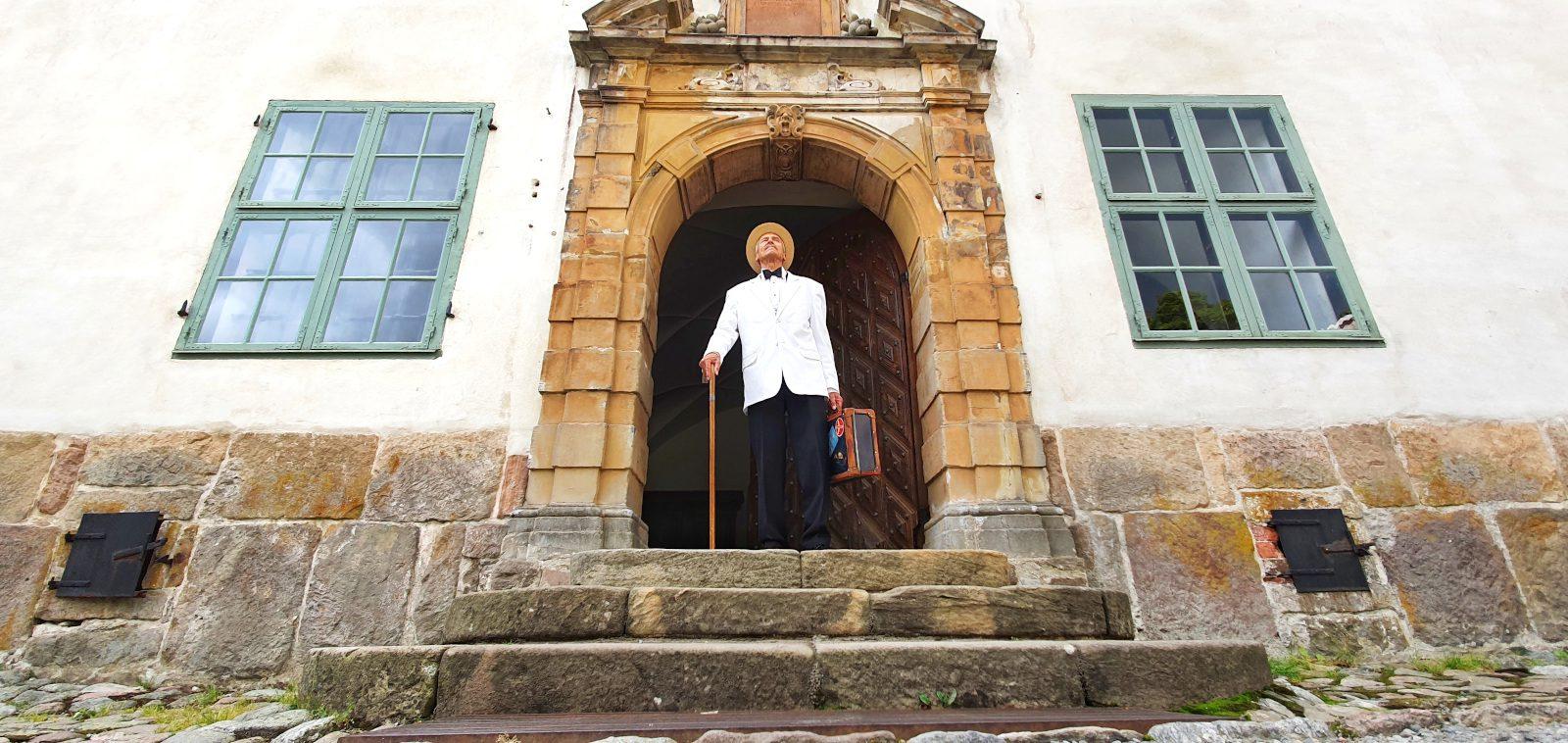 Louhisaaren kartanon koristeellisen kivisen pääoven edessä seisoo Mannerheimiksi pukeutunut miesnäyttelijä Petri Rajala, valkoinen takki päällä, kävelykeppi ja matkalaukku käsissään.