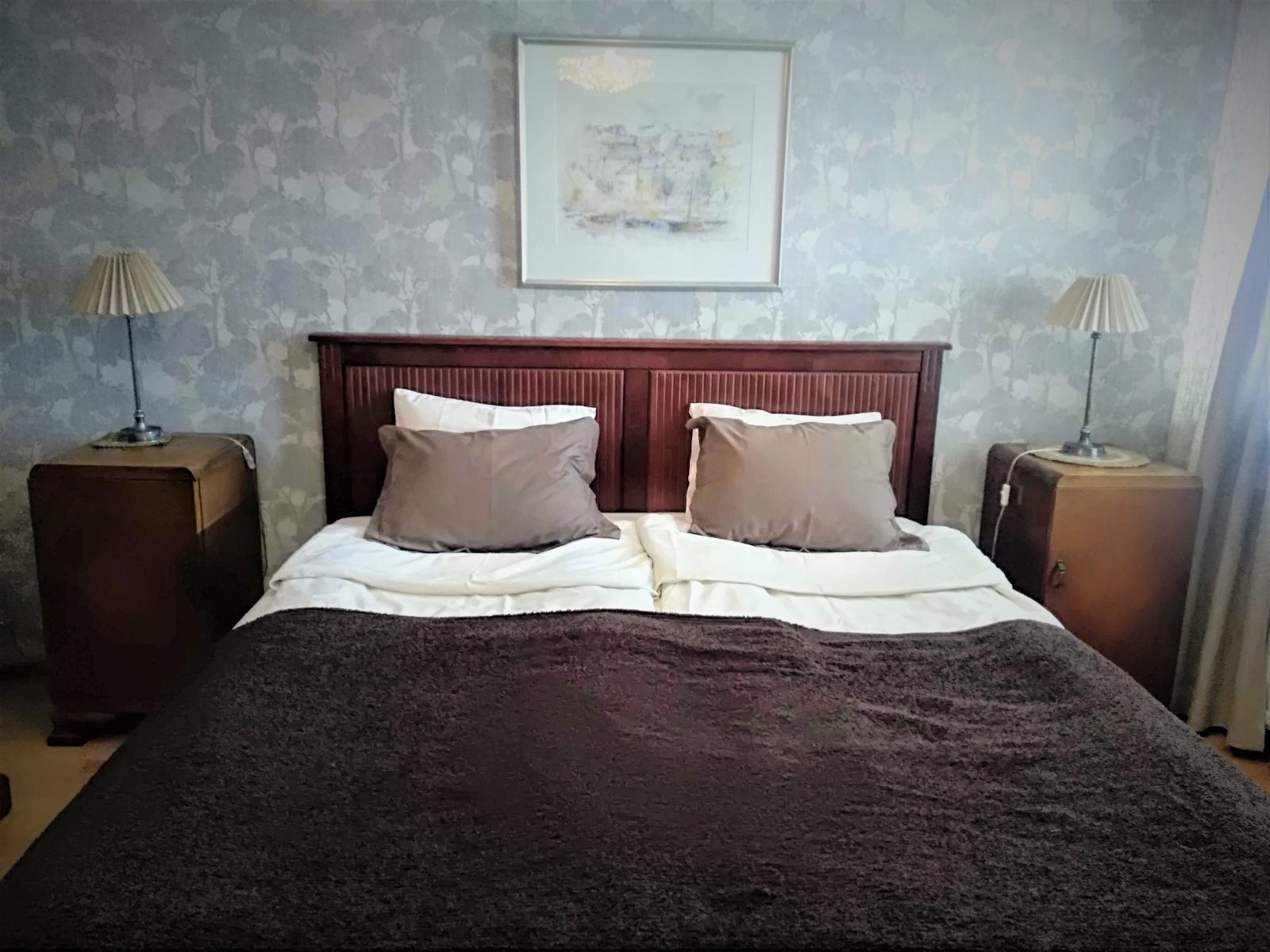 Makuuhuoneen parivuode, ruskea päiväpeitto ja valkoiset lakanat, harmaa seinä ja maisemataulu.