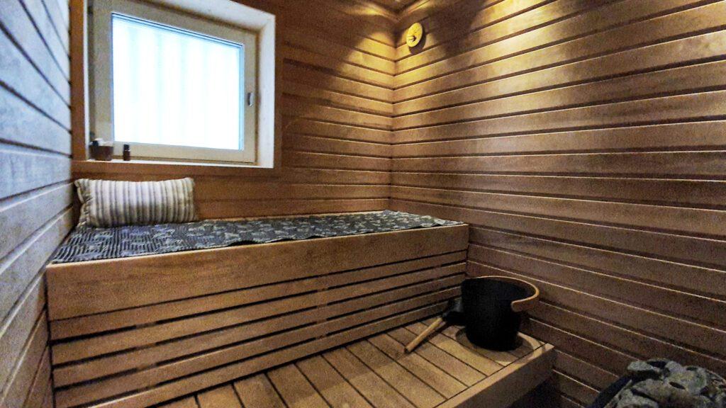 Huoneisto Merikorte sauna, harmaa laudeliina ja musta kiulu.