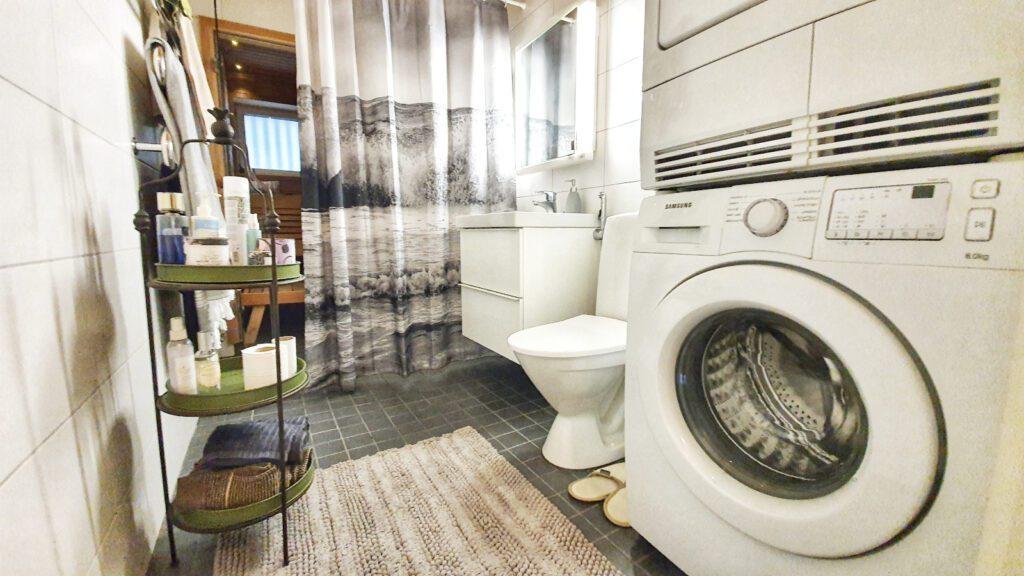 Kylpyhuone, jossa harmaat pinnat, mustavalkoinen suihkuverho ja pesukone.