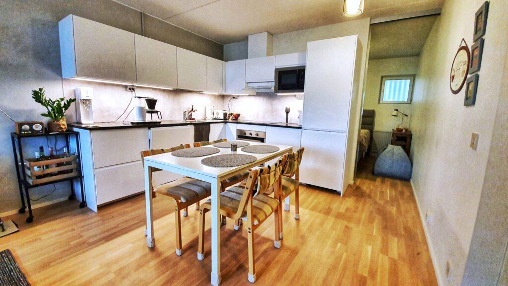 Huoneisto Merikorte keittiön pöytä ja kulmakeittiö taustalla.