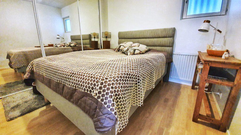 Huoneisto Merikorte makuuhuone, jossa parivuode harmaavalkoisella päiväpeitolla.