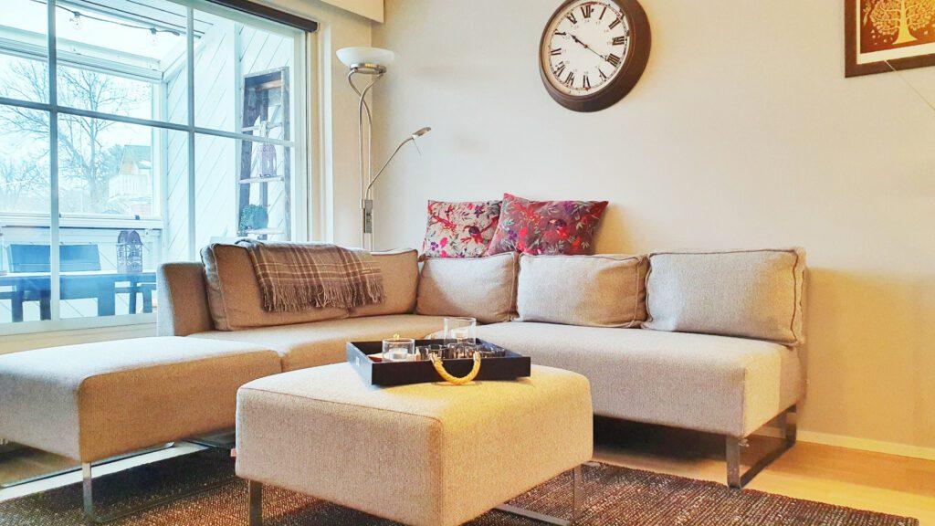 Huoneisto Merikorte olohuone, ikkuna ja kulmasohva sekä sohvapöytä.
