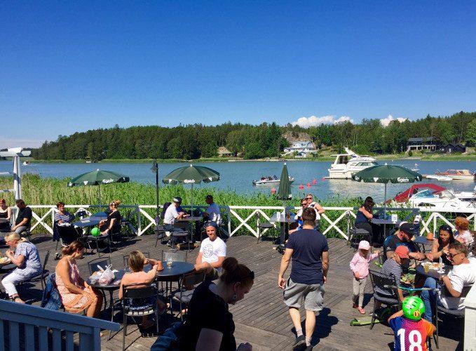 Merimaskun Rantamakasiinin terassi ja asiakkaita aurinkoisena kesäpäivänä.