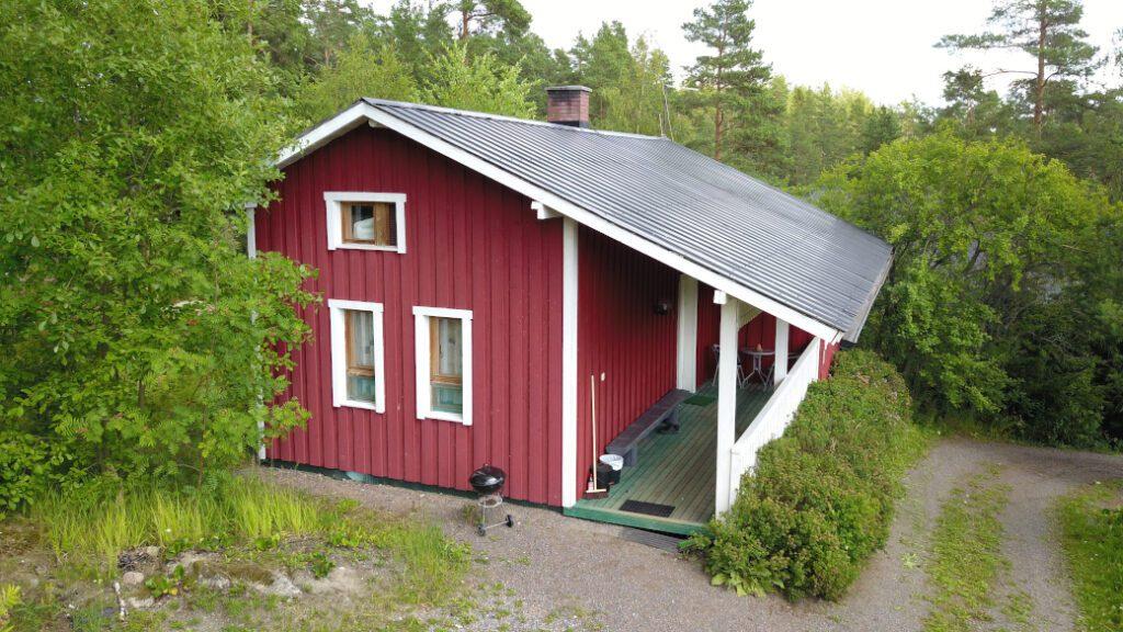 Lomahyppäykyksen punainen mökki numero 5 verheän puutarhan keskellä, vihreä terassi ja valkoiset kaiteet.