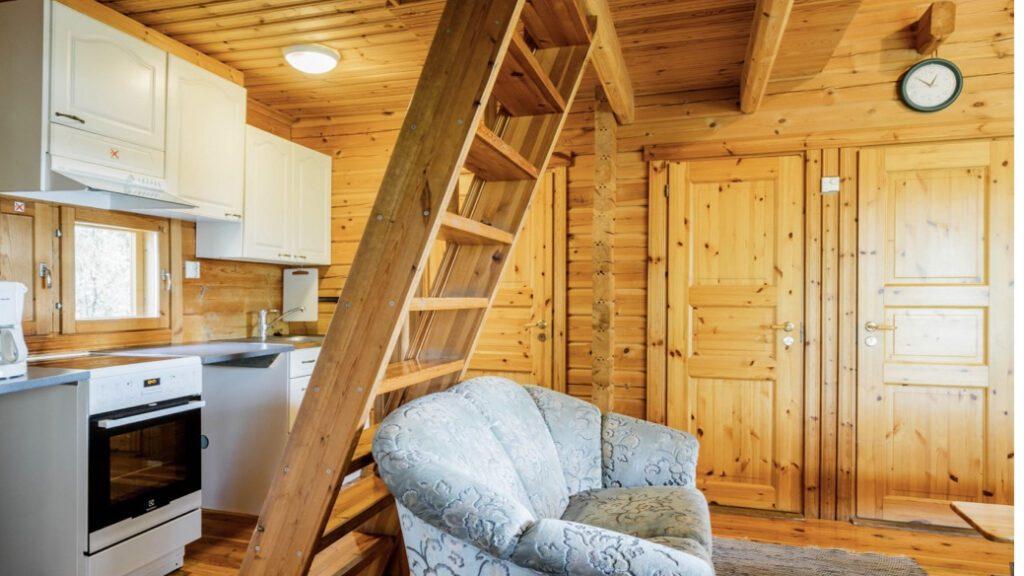 Lomahyppäyksen mökin 6, 11 tai 12 sisätila, puiset seintä, raput parvelle, sohva ja keittiönurkkaus.