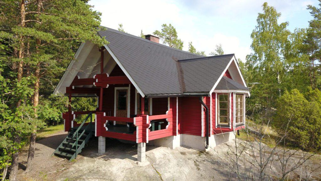 Lomahyppäyksen punainen hirsi mökki 7 tai 8 metsäisen kalliotasanteen päällä.