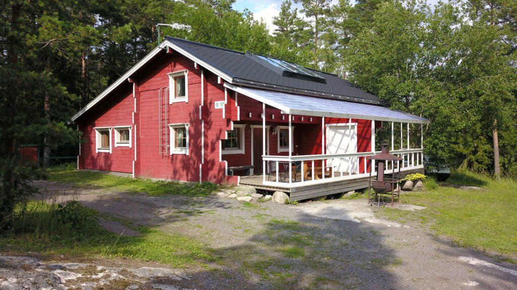 Lomahyppäyksen iso punainen mökki 9 tai 10, kaksikerroksinen, iso terassi ja valkoiset puitteet.