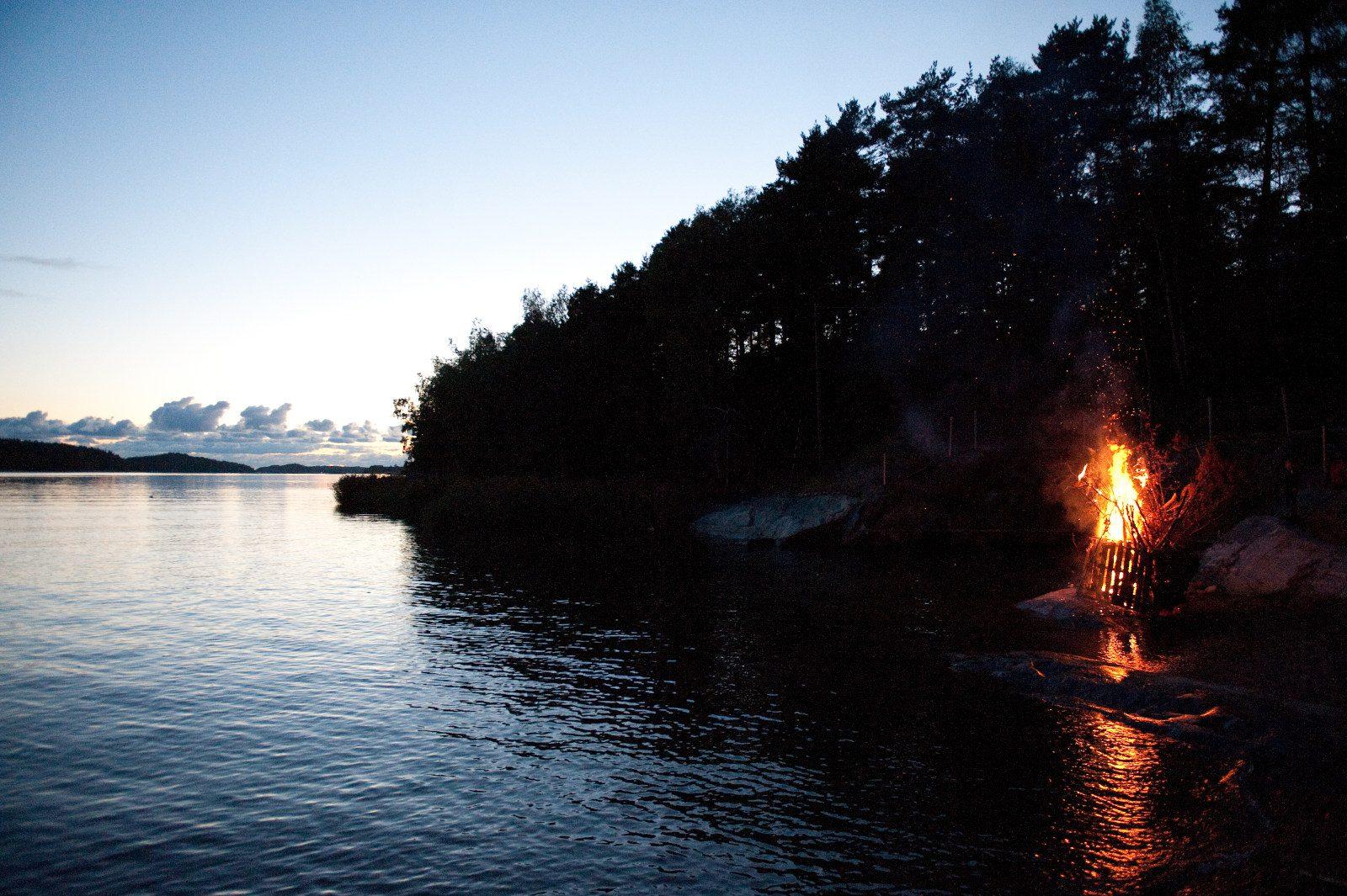 Saaristo ja luonto Naantalissa jamerenranta iltahämärässä, rannalla palaa muinaistuli.