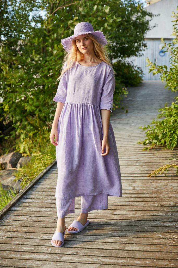 Muoti-Kulma Krisse mallinainen lilassa mekossa ja hatussa kävelee laiturilla.