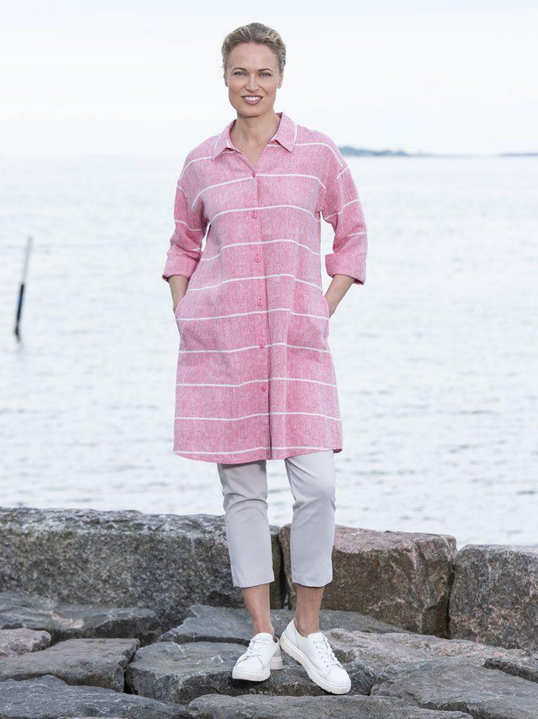 Muoti-Kulma Krisse mallinainen vaaleanpunaisessa takissa meren rannalla.