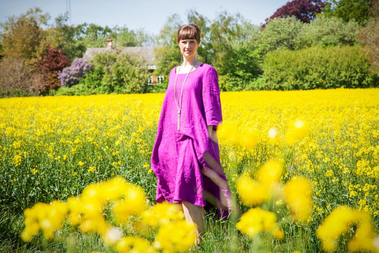 Muoti-Kulma Krisse mallinainen violetissa mekossa keltakukkaisen pellon keskellä.