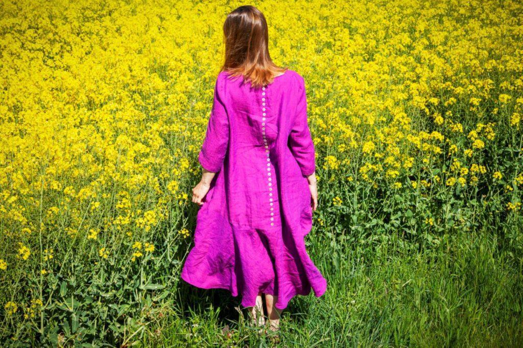 Muoti-Kulma Krisse mallinainen violetissa mekossa keltakukkaisen pellon laidalla selkä päin kameraa.