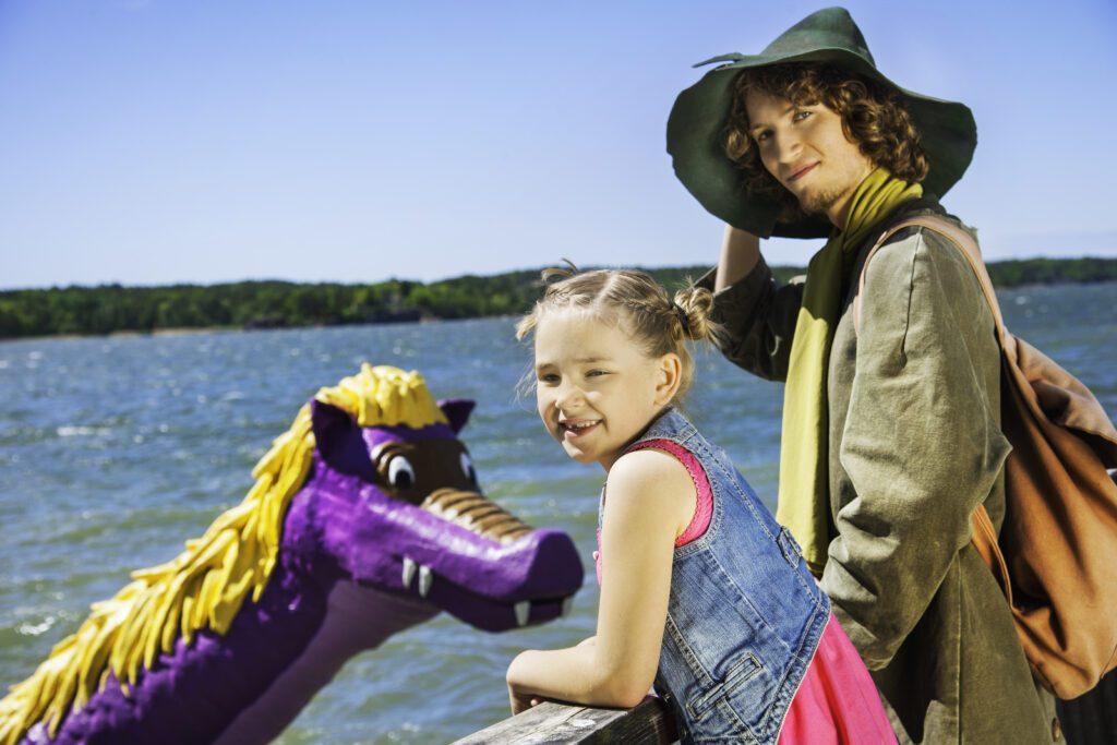 Lapsi ja Nuuskamuikkunen hymyilevät laiturilla, Drontti Edvardin pää näkyy taustalla merimaisemaa vasten.