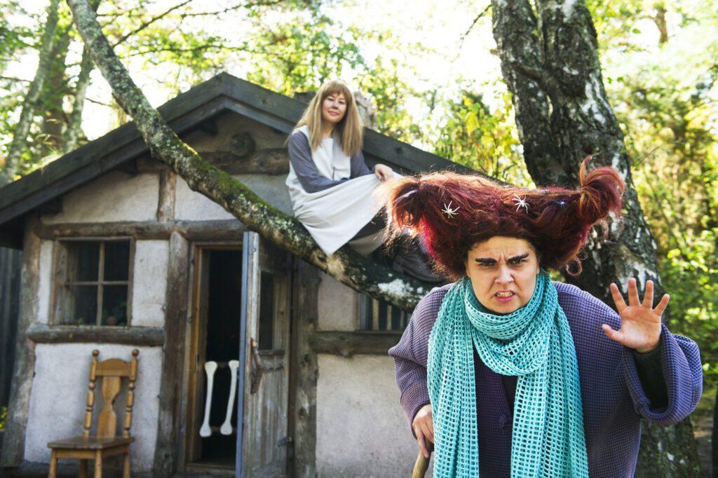 Muumimaailman noita irvistää edessä, Aliisa istuu taustalla puun oksalla.
