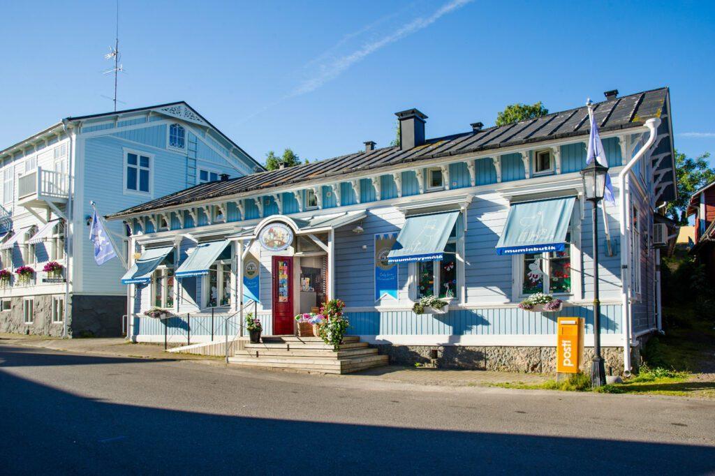 Vaaleansininen Muumimyymälän puutalo kadun varrella. Ovi auki, ikkunassa muumin kuvia.