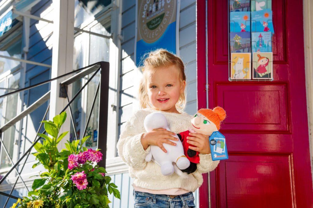 Pieni tyttö pitää kädessään Niiskuneiti ja Pikku Myy -pehmoleluja. Tyttö seisoo Muumimyymälän punaisen oven edessä.