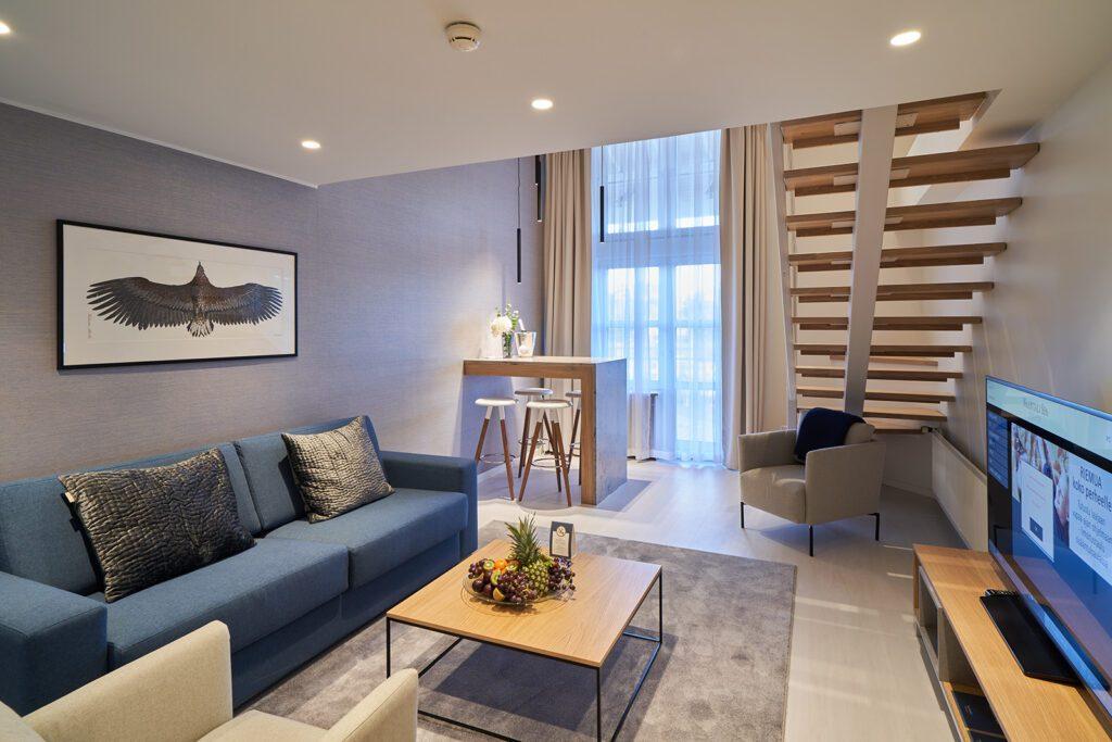 Naantalin Kylpylän teemasviitti, sininen sohva, sohvapöydällä hedelmiä, huoneen takaosassa baaripöytä ja tuolit, ikkuna ja portaa yläkertaan.