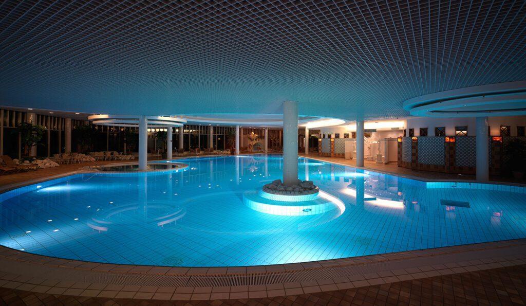Naantalin Kylpylän allaosasto pimeällä, valaistu altaan vesi kirkkaan sininen.