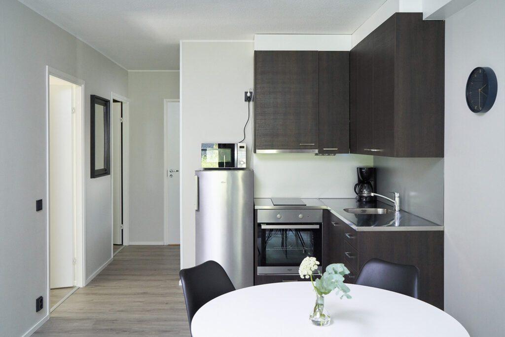 Naantali City Apartmentsin keittiö, jossa näkyy tummat keittiön kapit, uuni, harmaa jääkaappi ja pyöreä valkoinen pöytä.
