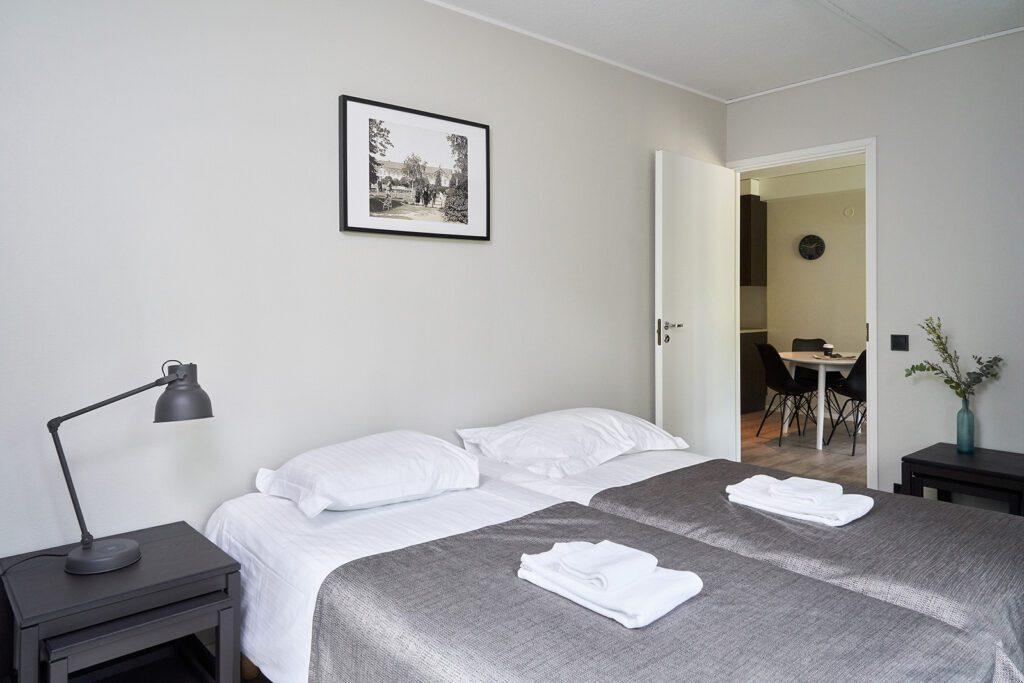 Naantali City Apartments huoneiston makuuhuone, kaksi vuodetta, jonka päällä hopeinen päiväpeitto ja pyyhkeet.