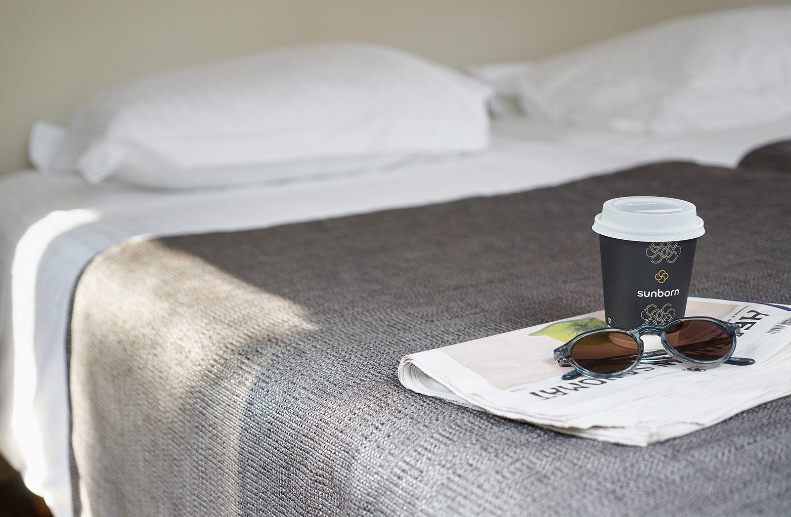 Naantali City Apartmentsin sänky, jonka päiväpeiton päällä sanomalehti, take away -kahvikuppi ja aurinkolasit.