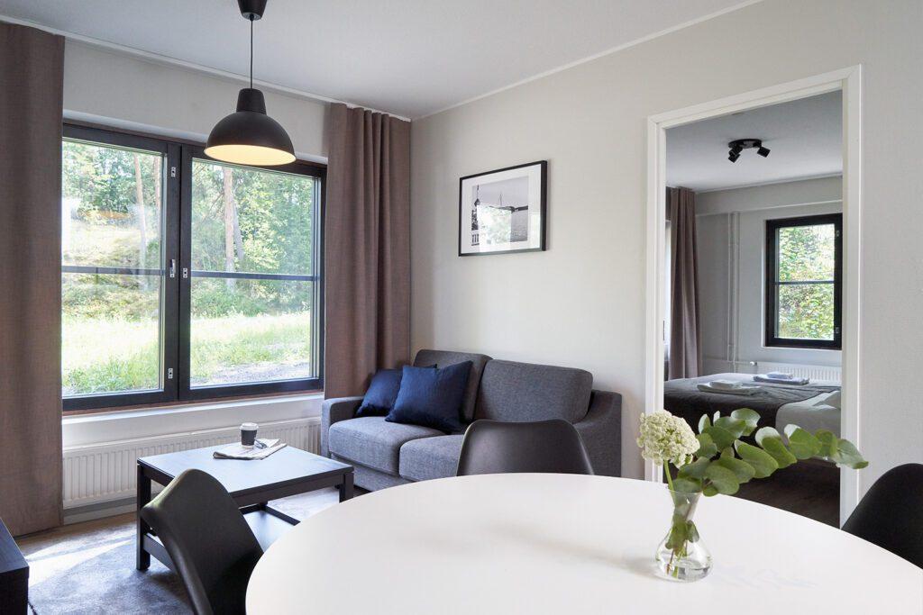 Naantali City Apartmentsin oleskelutila, valkoinen pöytä, harmaa sohva, sohvapöytä. Avonaisesta ovesta näkyy makuuhuoneeseen, jonka sänkyjen päällä pyyhkeet.