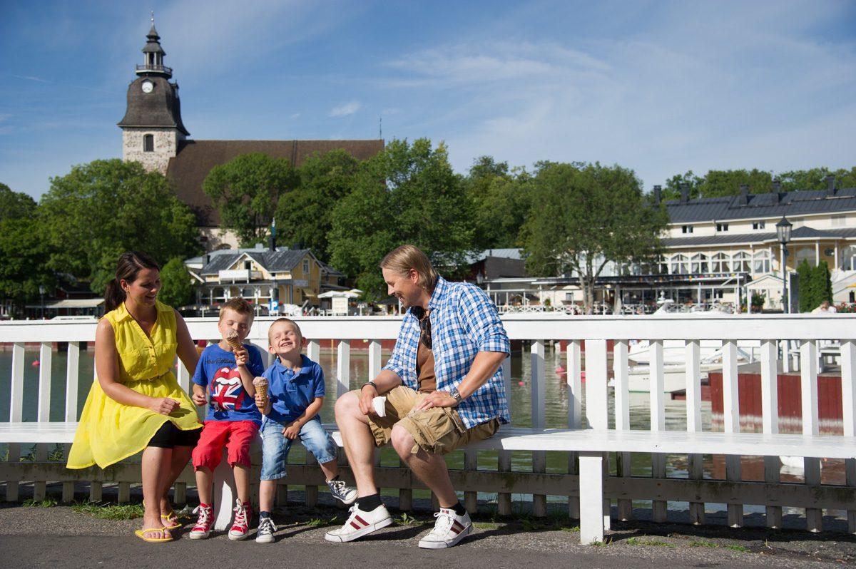 Keltamekkoinen äiti, kaksi poikaa ja sinipuseroinen isä istuvat penkillä ja syövät jäätelöä. Takana valkionen kaiden ja taustalla Naantalin kirkko sinistä taivasta vasten.