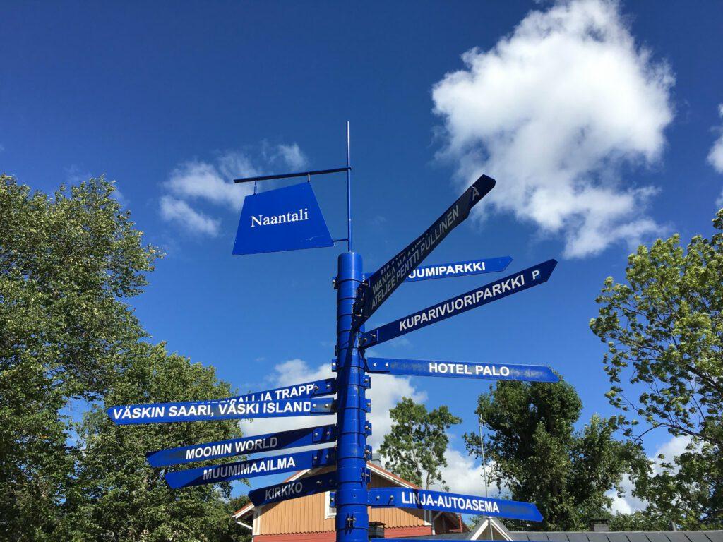 Sininen pylväs, jossa viittoja eri suuntiin, huipulla lukee Naantali. Taustalla sininen taivas, jolla muutama pilvi.