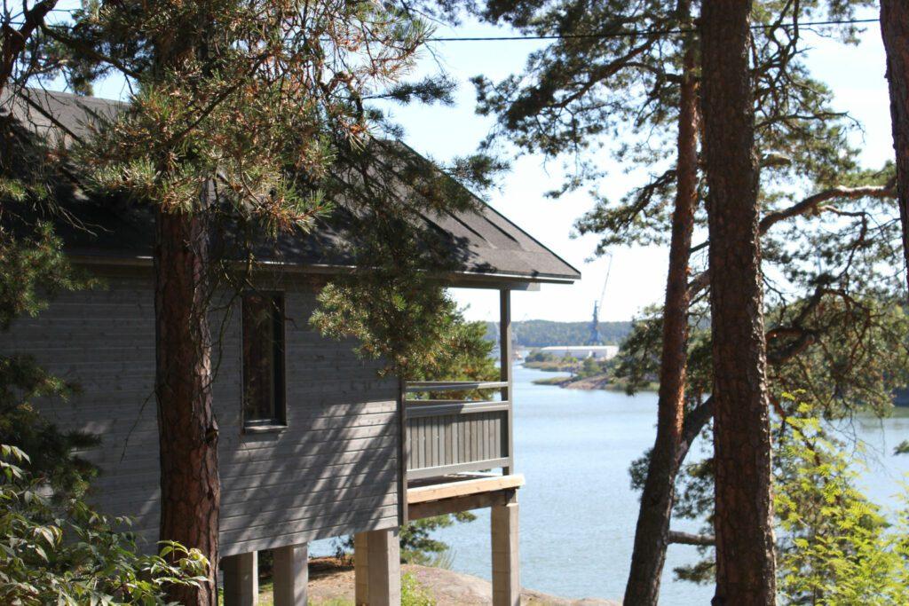 Harmaa leirintäaluemökki meren rannalla ja puiden ympäröiomänä.