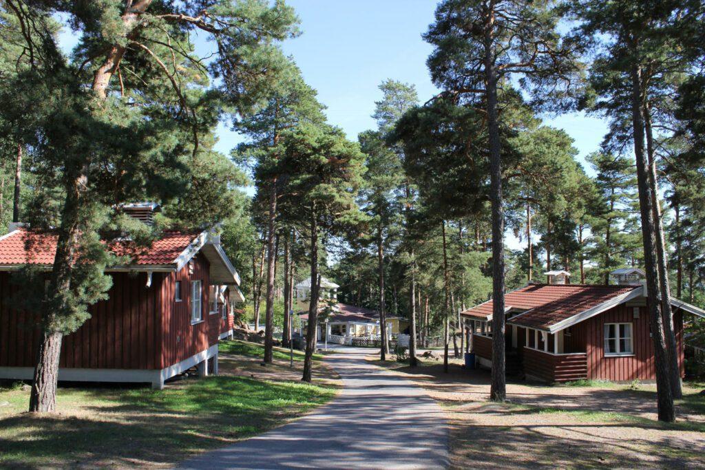 Naantali Campingin punaisia mökkejä, tie menee keskellä, puita ympärillä.