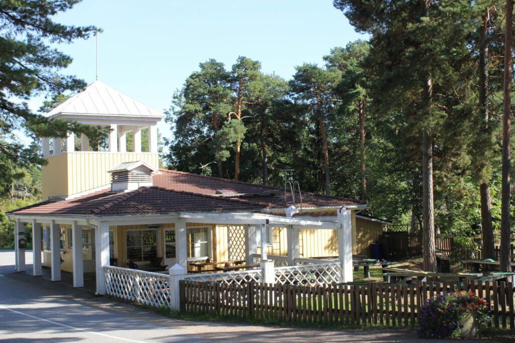 Naantalin Campingin keltainen vastaanottorakennus ja teassi. Aurinkoinen kesäpäivä, sinistä taivasta ja metsää taustalla.