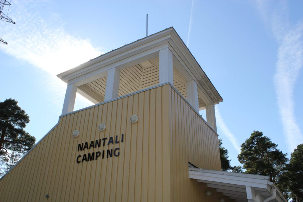 Naantalin Campingin vastaanottorakennuksen keltainen torni, seinässä lukee Naantali Camping.