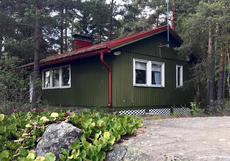 Vihreä mökki metsän keskellä, punainen katto ja saderänni.