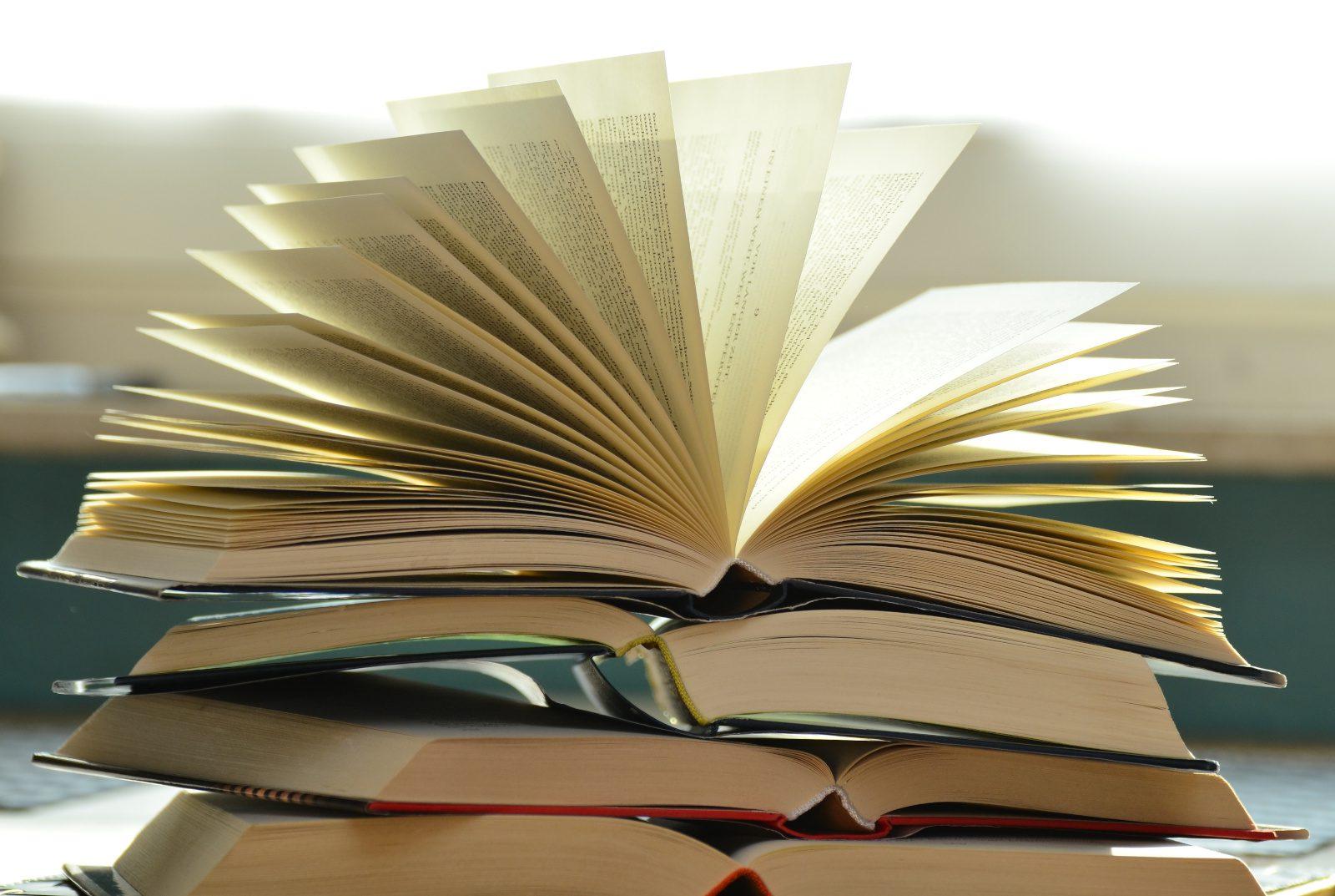 Kirjapinon päällä aukinainen kirja, jonka sivut ovet kaarevasti auki.