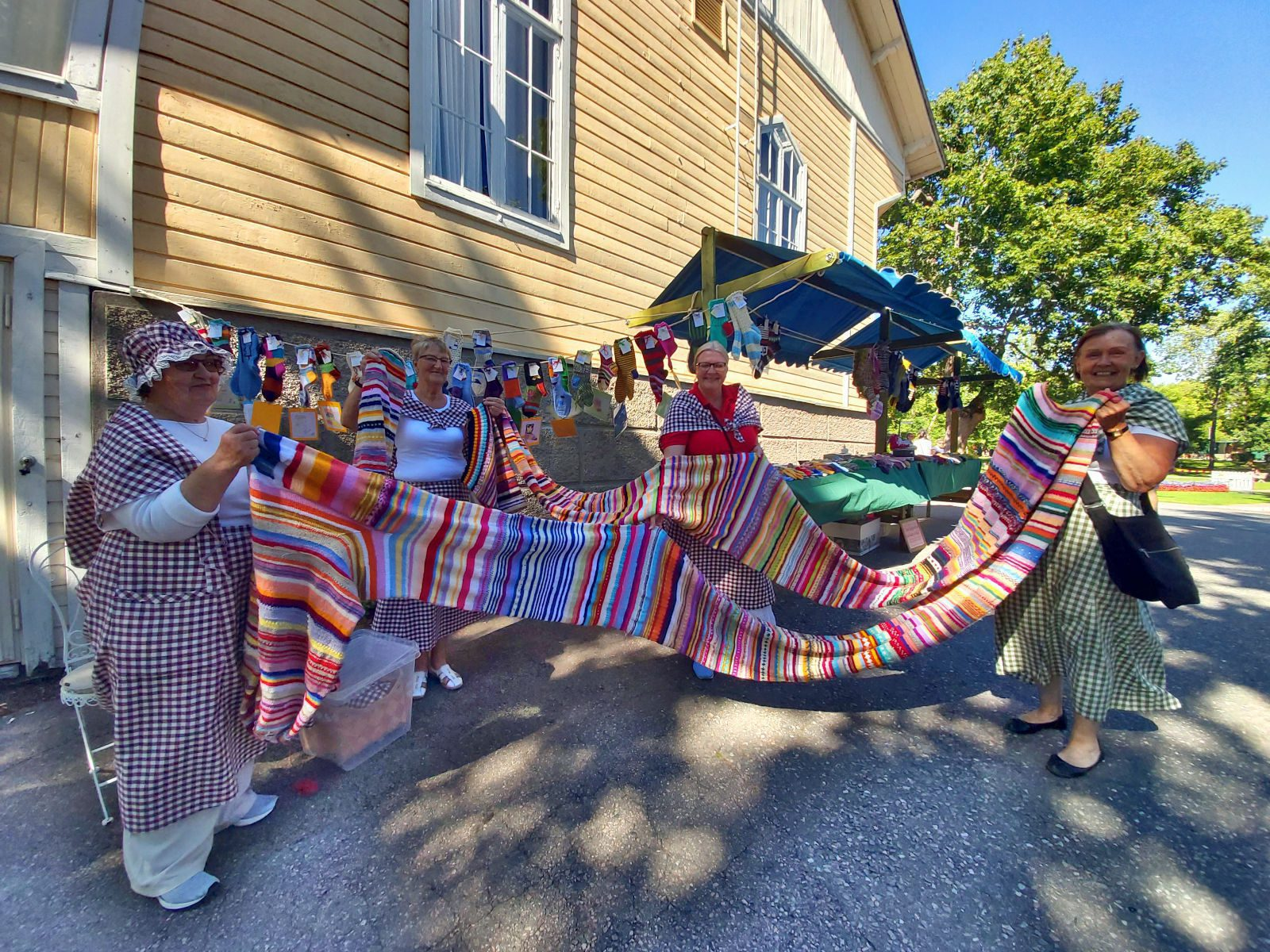 Neljä Naantalin aurinkoista sukkamatamia pitävät käsissään monta metriä pitkää kudottua raidallista jättisukkaa.
