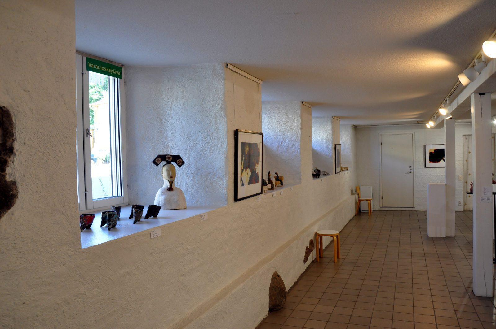 Naantalin Taidehuoneen valkoinen sisäseinä ja ikkunasyvennykset, joissa keramiikkataidetta esillä.