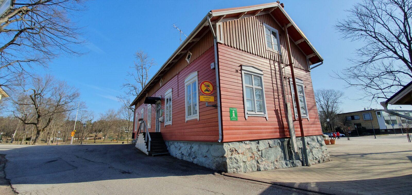Punainen puurakennus, jonka nurkassa on vihreä info-kyltti. Portaat ylös ovelle, valkoiset ikkunankarmit. Sininen taivas.