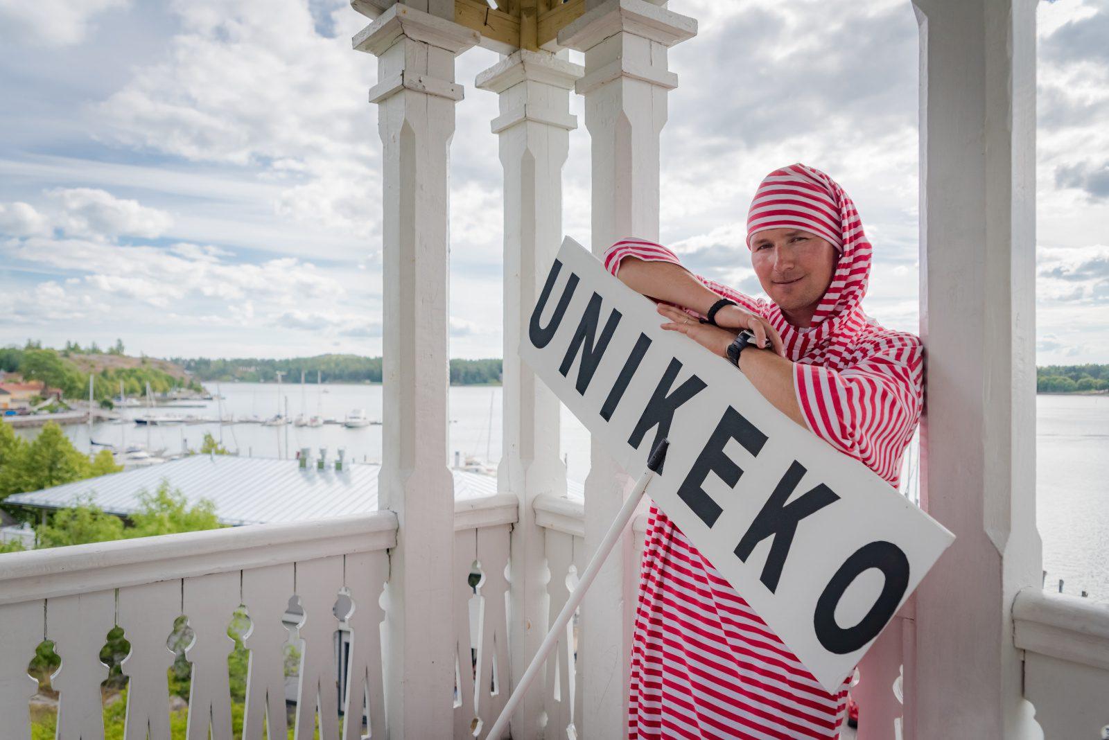 Mies Unikeko-puvussa nojailee näkötornin kaiteeseen Unikeko-kyltin kanssa. Taustalla merenlahti.