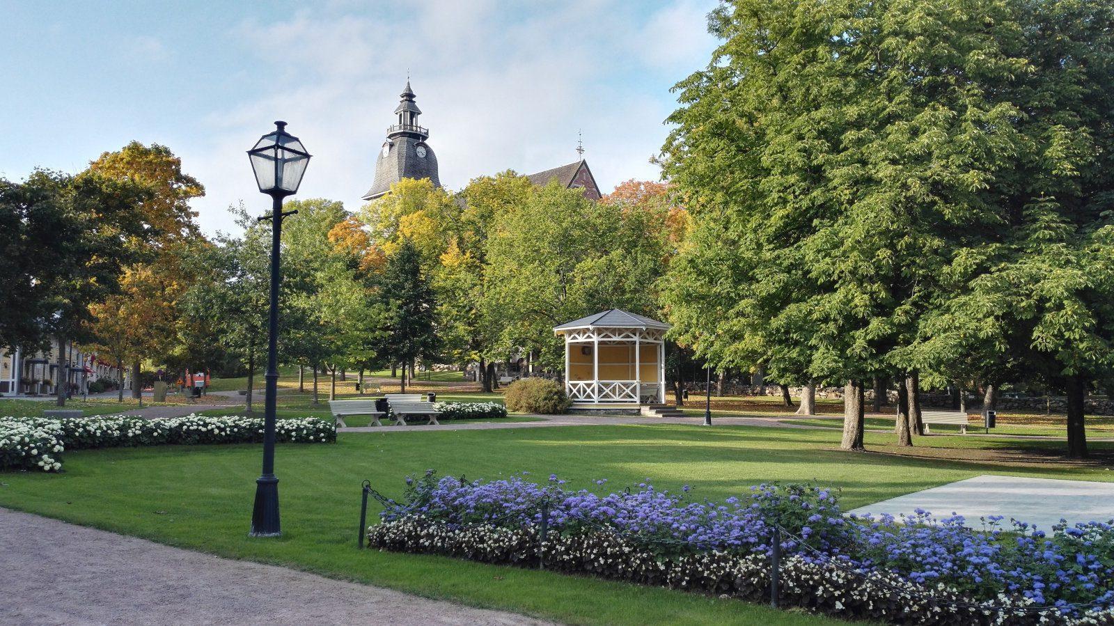 Naanatlin kirkkopuisto loppukesällä, sinisiä kukkia, keltainen paviljonki ja Naantalin kirkko puiden takana.
