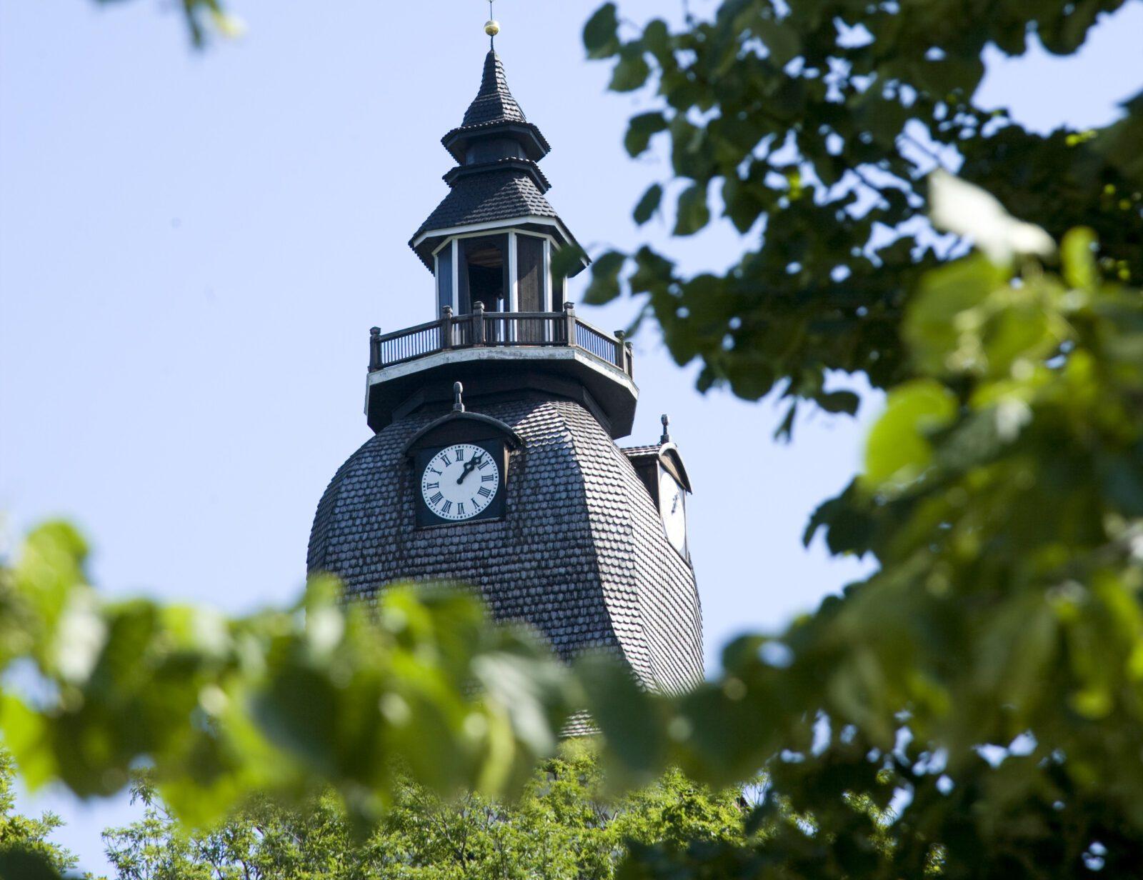 Naantalin kirkon torni puiden lehvien läpi.