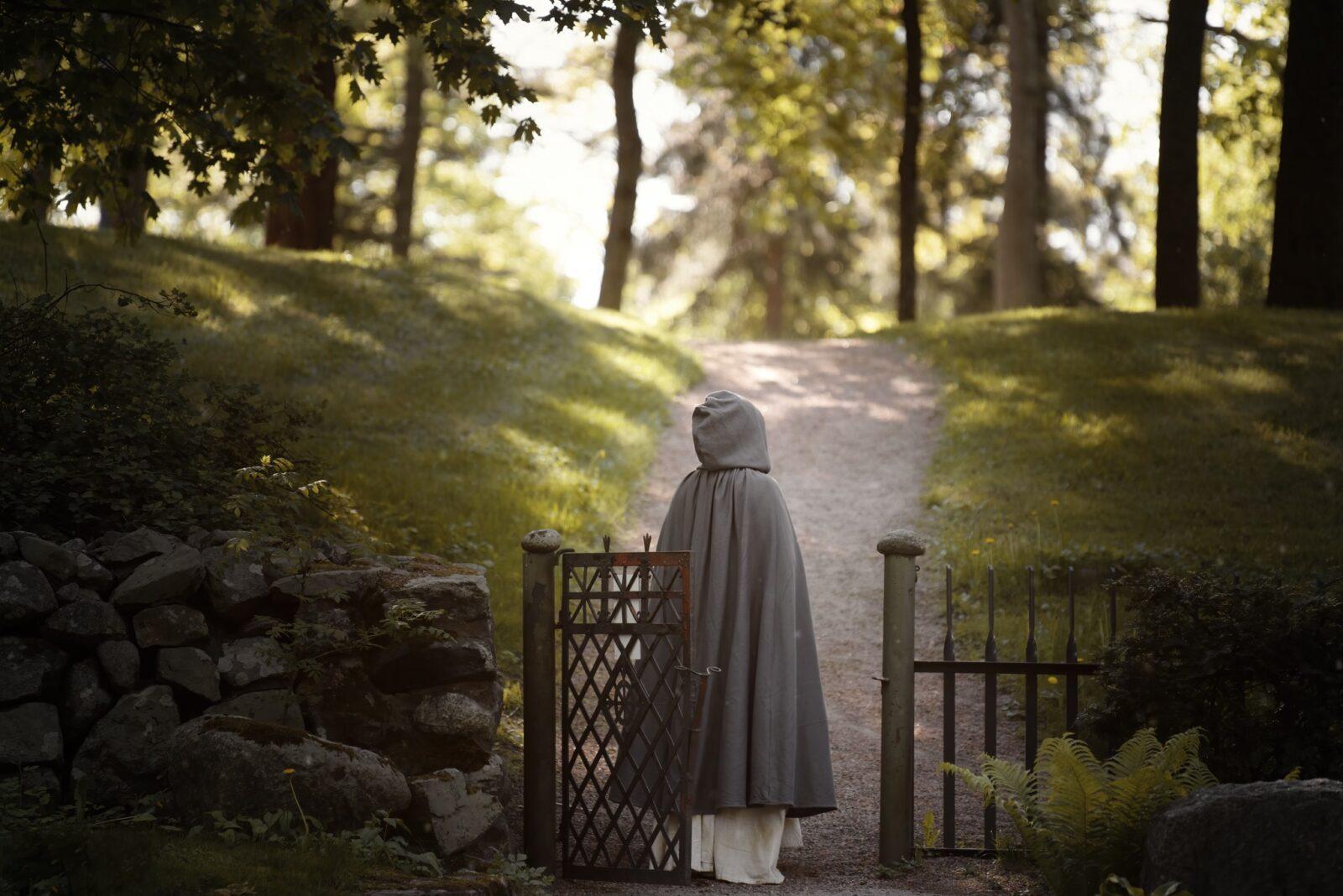 Naantalin luostaripäivien henkilö viittaan pukeutuneena Naantalin kirkon luona.