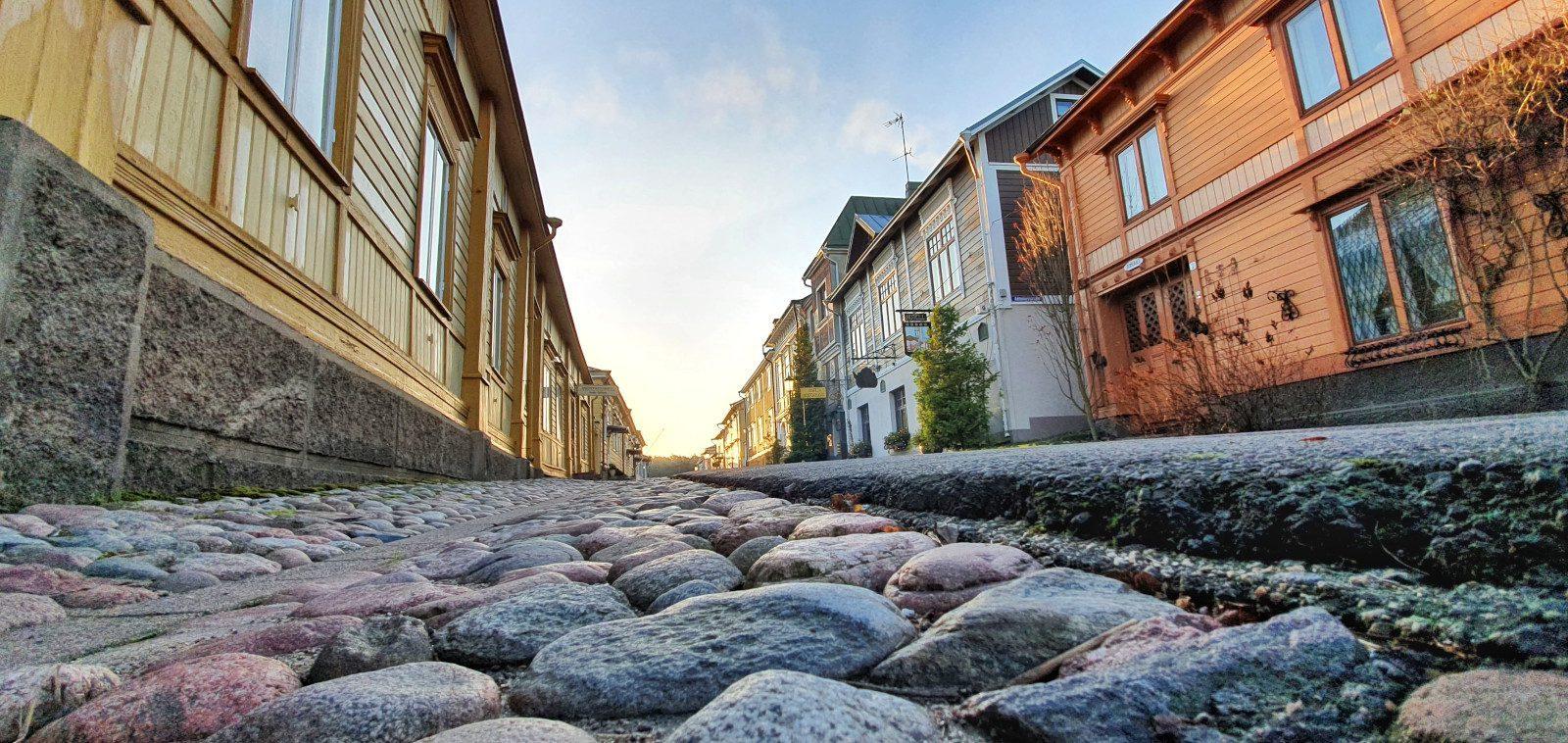 Katutasolta kuvattu näkymä Naantalin vanhan kaupungin Mannerheiminkadulle. Mukulakivetys ja oranssin ja keltaisen sävyisiä puutaloja.