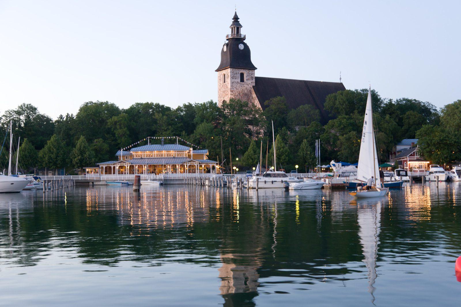 Naantalin kirkko ja merenlahti, tyyni kesäilta. Vierasvenesatamaan purjehtii purjevene.