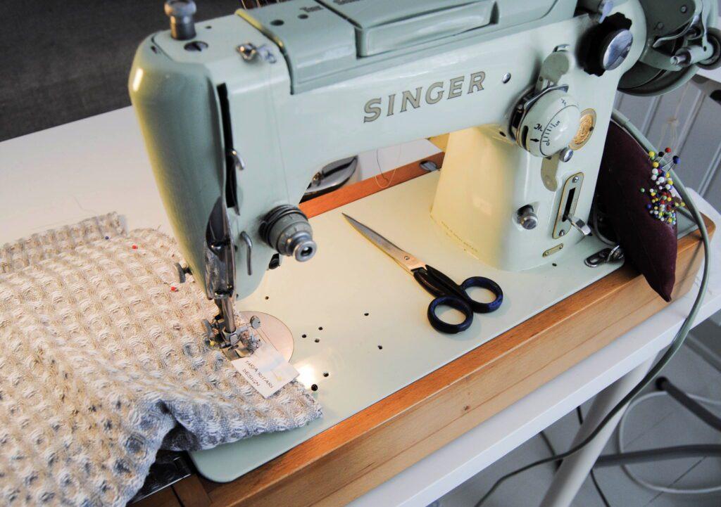 Tarja Ritari Designin työhuoneen Singerin ompelukone, jossa vohvelipyyhe ja sakset.
